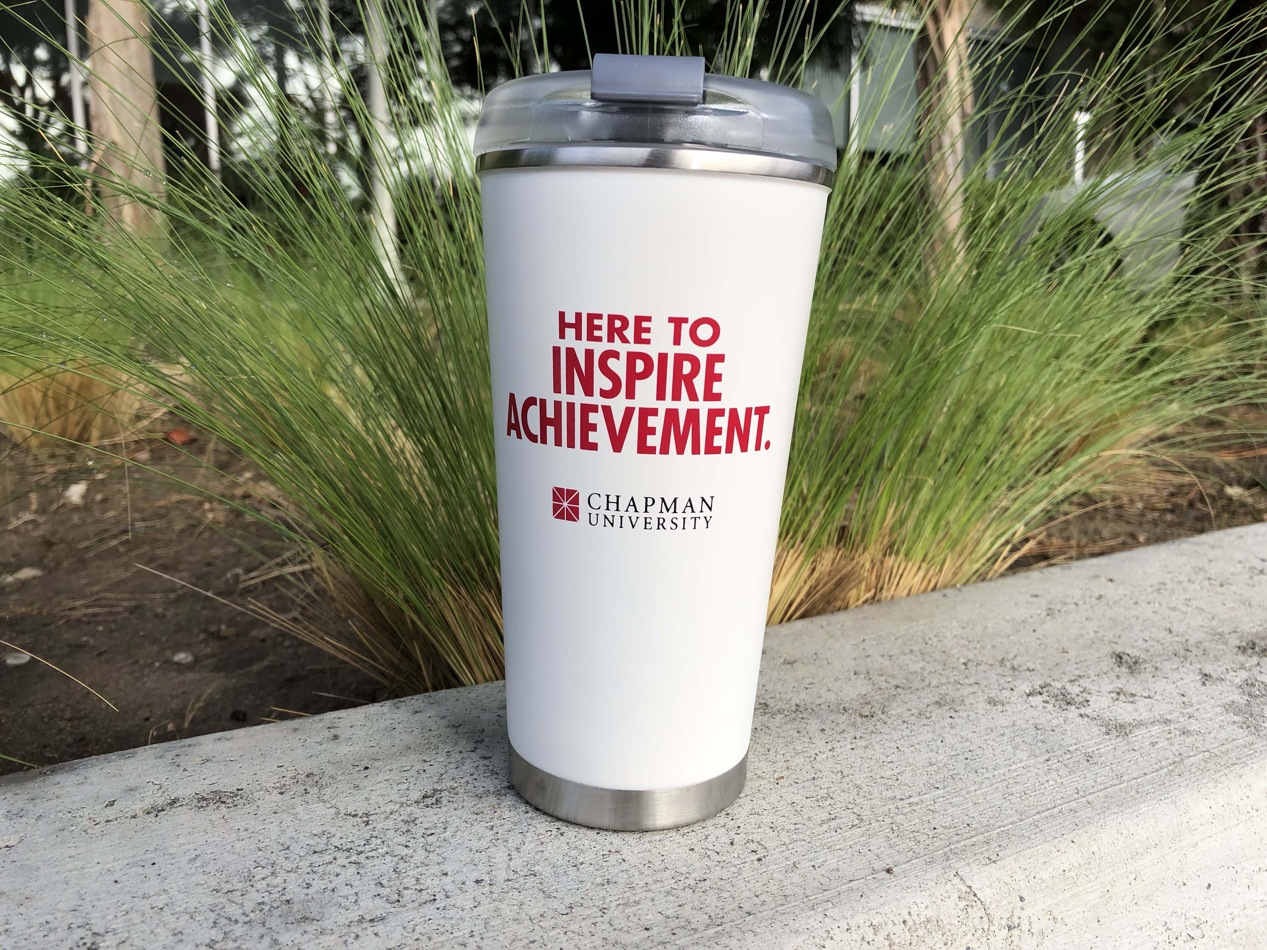 """white metal mug with slogan """"here to inspire achievement."""" and a Chapman University logo"""