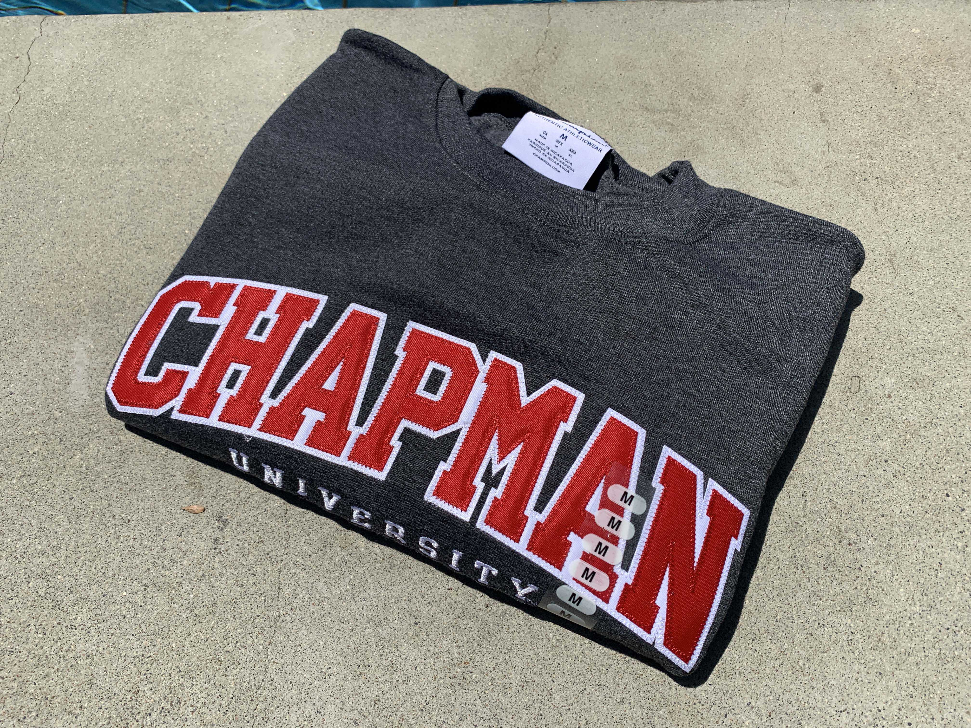 folded sweatshirt with the words Chapman University on the front