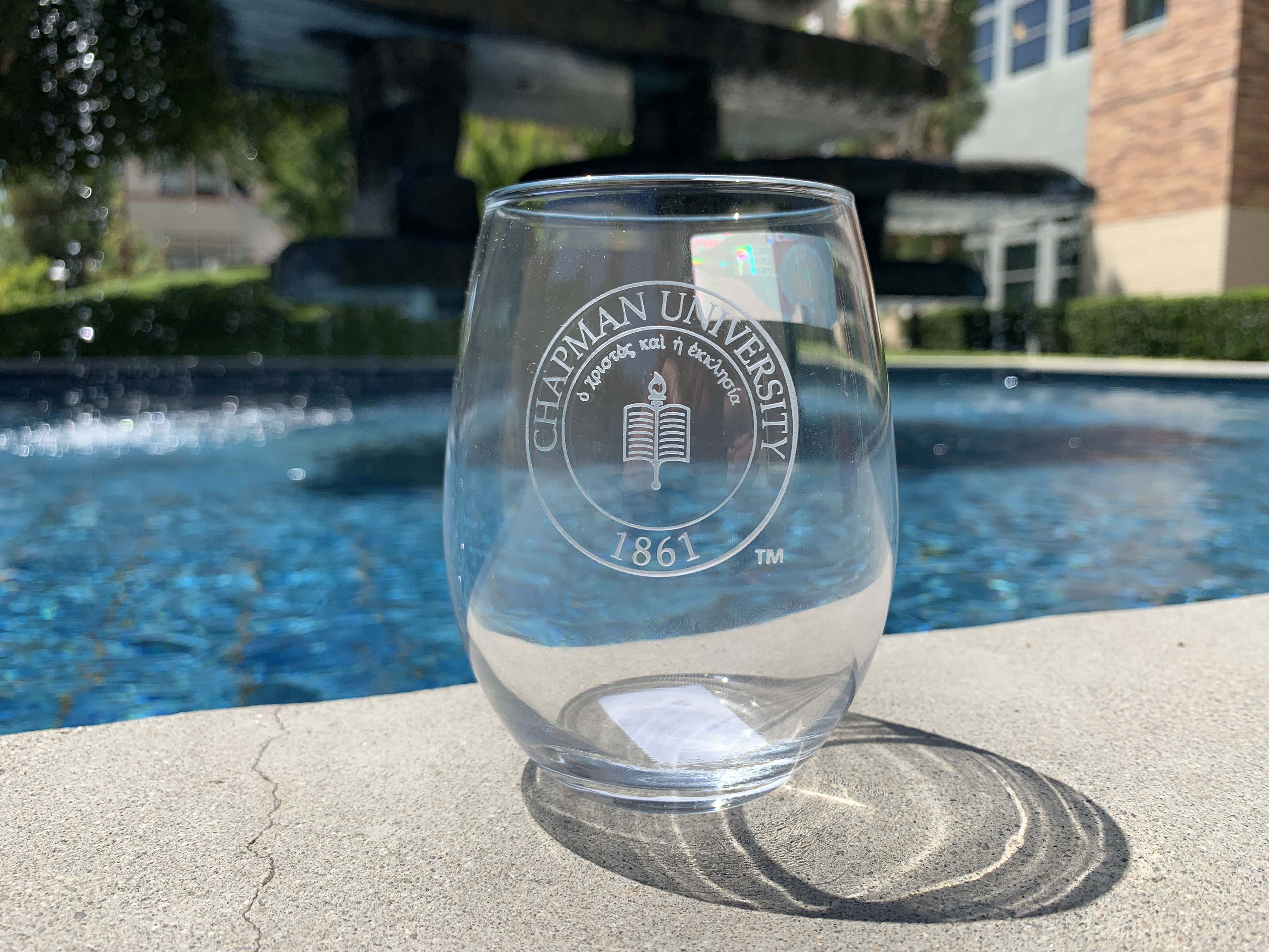 drinking glass with chapman university crest etched on the front
